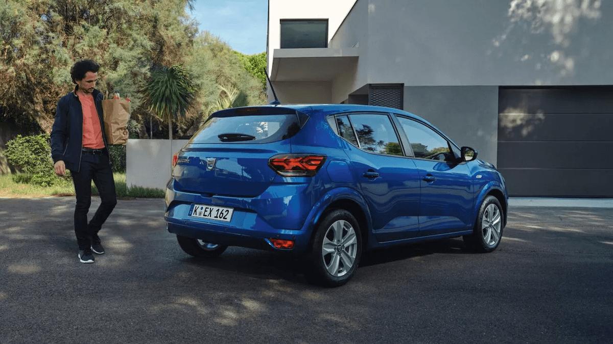 Heckansicht vom blauen Auto - Mann trägt seinen Einkauf zum Auto - Dacia Sandero - Renault Ahrens Hannover