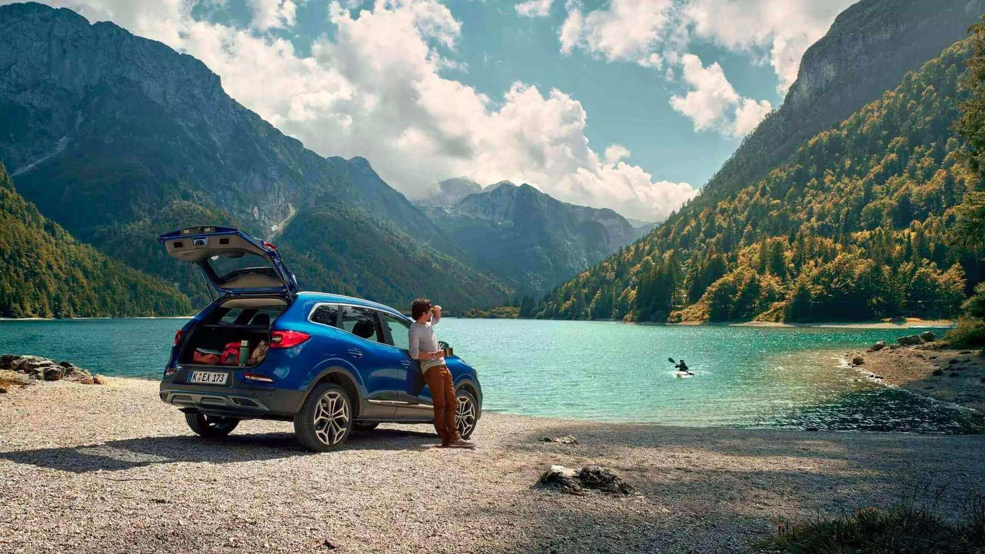 Heckansicht Kofferraum geöffnet - Blaues Auto steht an einem See mit Bergen- Auto fährt in einer Kurve - Renault Kadjar - Renault Ahrens Hannover