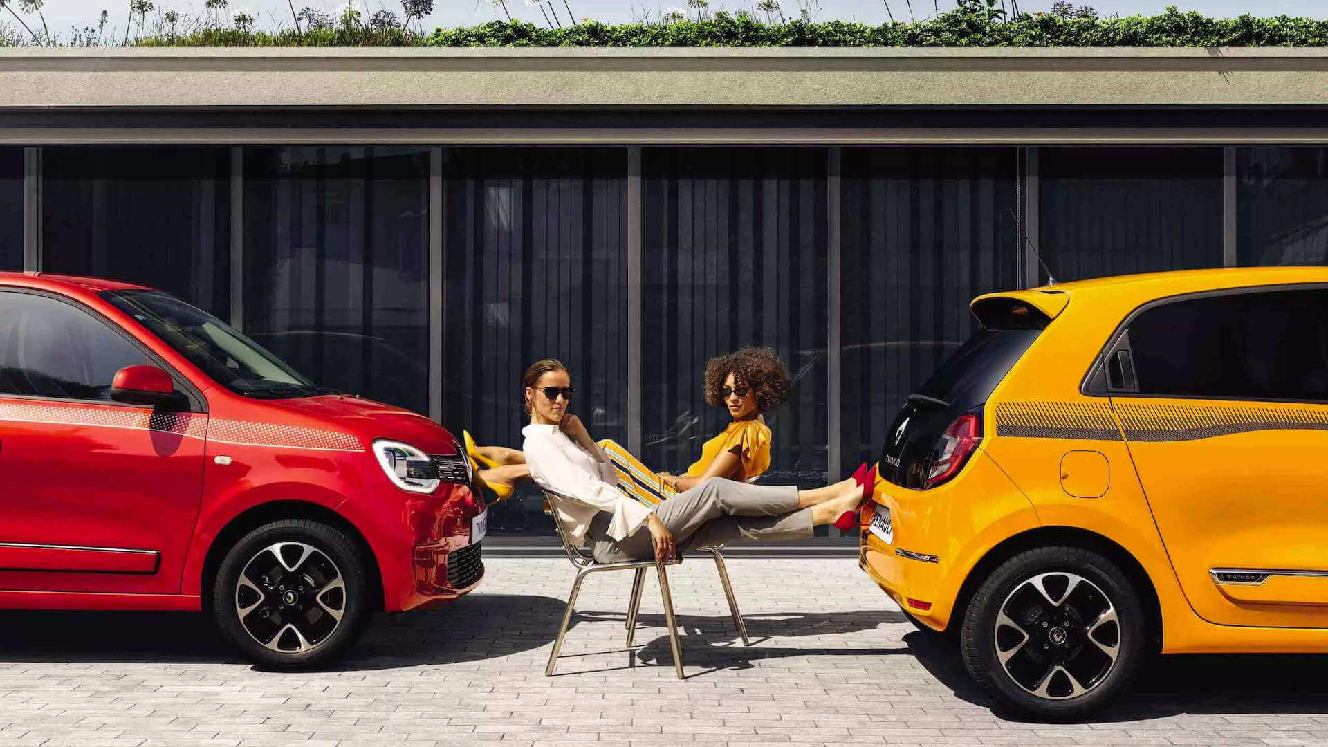 Seitenansicht von zwei Autos- Frauen Sitzen auf zwei Stühlen zwischen den Autos - Renault Twingo - Renault Ahrens Hannover