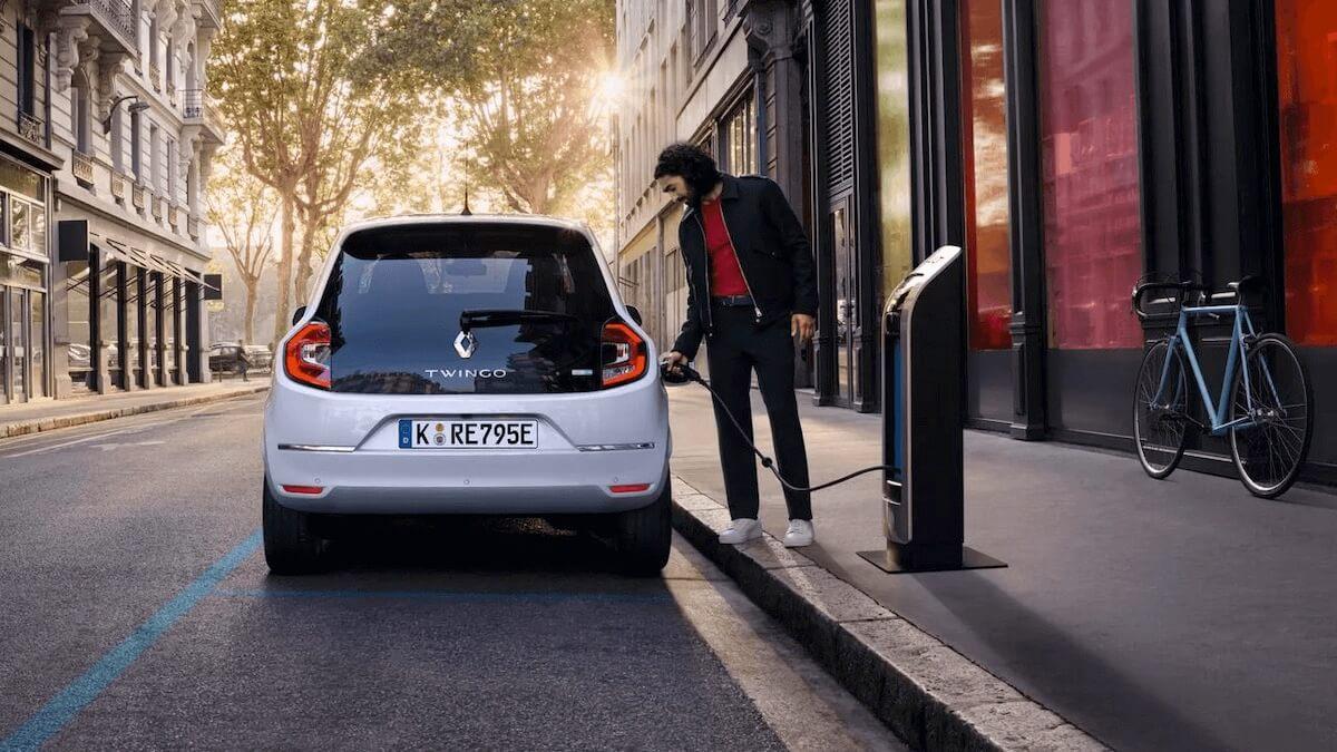 Mann lädt auto an eine Elektro Ladestation auf der Straße- Renault Twingo Electric - Renault Ahrens Hannover